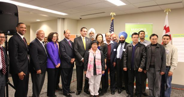 Mayor Gray and OAPIA Director Julie Koo pose with AAPI small business owners and other district agency directors