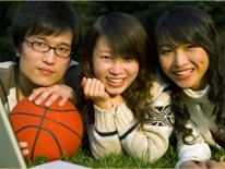 3 aapi youths reclining on grass with basketball
