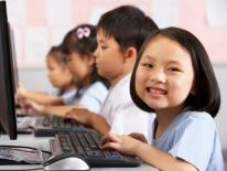 Asian girl smiling while working at her pc in schoolroom with other Asian students