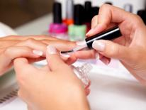A manicurist's hands visable while applying clear polish to a woman's fingernails