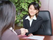 Asian businesswoman interacting at a desk with a female OAPIA representative