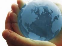 light blue glass globe held in hands